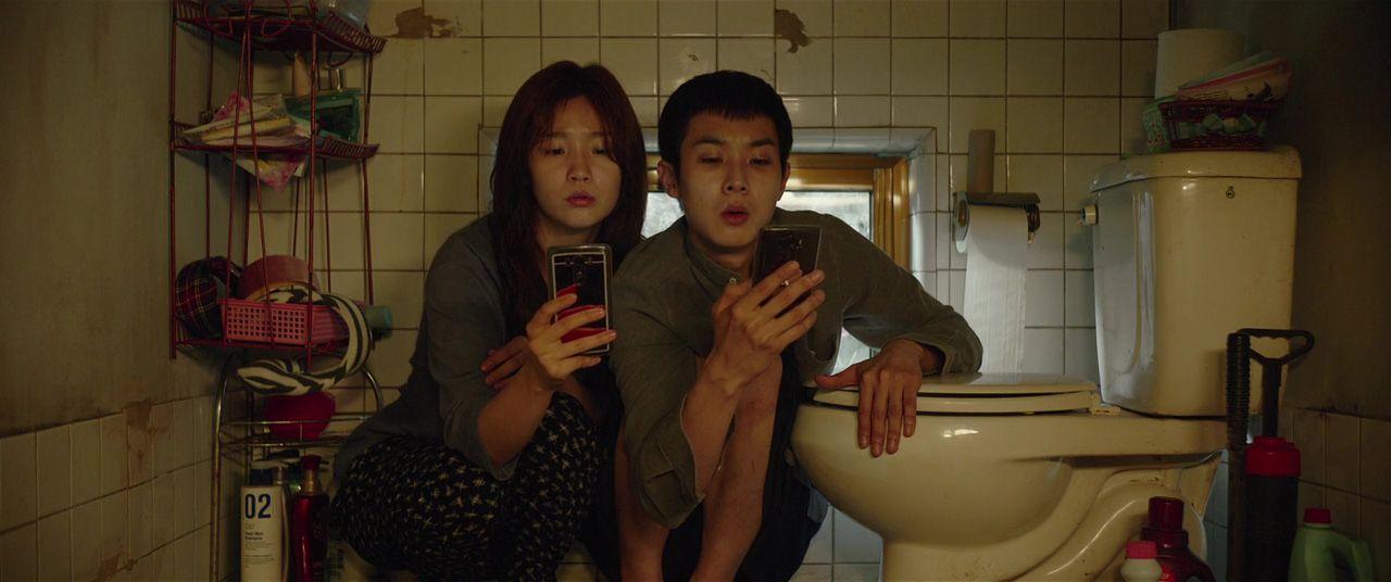 Scena iz filma Parazit: likovi hvataju wi-fi dok čuče pokraj wc školjke