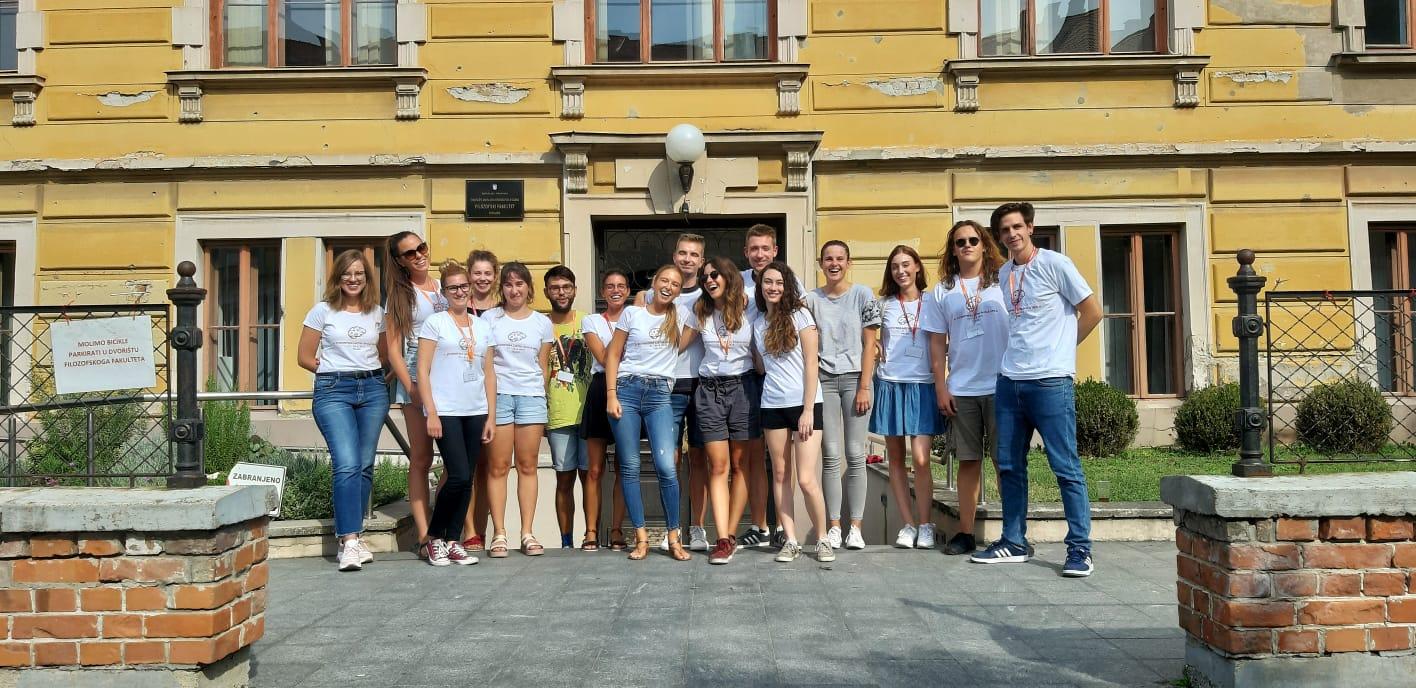 Slika prikazuje polaznike Ljetne škole koja se 2019. održavala u Osijeku, zagrljeni stoje ispred ulaza na Filozofski fakultet u Osijeku